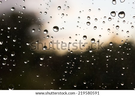 Raindrops on a window, with a stormy backdrop.