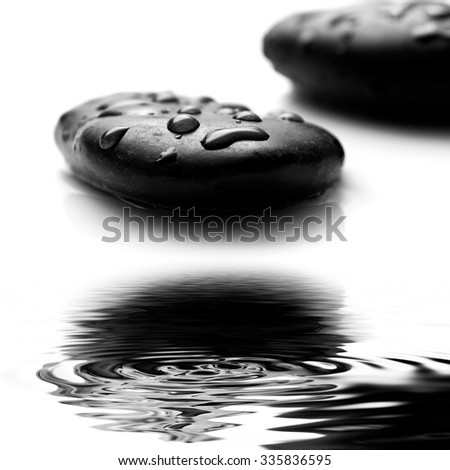 raindrops on black pebbles in border water reflection  - stock photo