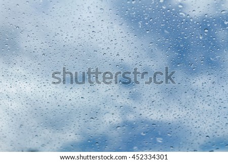 Raindrops on glass and blurred blue sky