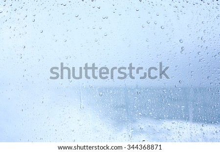 raindrops on glass, on a background of clouds - stock photo