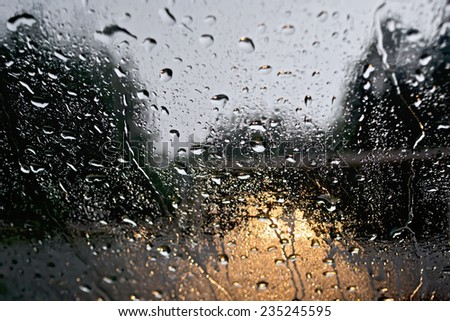 Raindrops on glass window with blurred trees, the road and the yellow lights of the car - stock photo