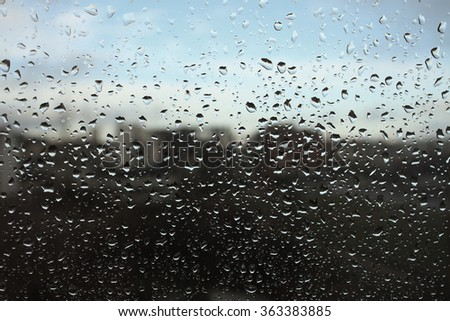 Raindrops on glass with blue sky and city in background