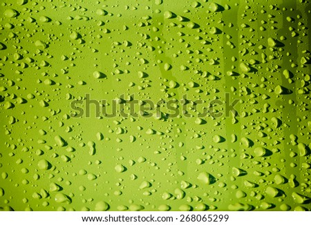 Raindrops on green metal surface - stock photo