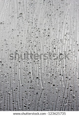 Raindrops on textured glass background - stock photo