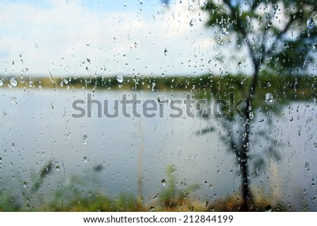 Raindrops on the glass through which the visible nature - stock photo