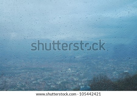 Raindrops on the window. City in the background.