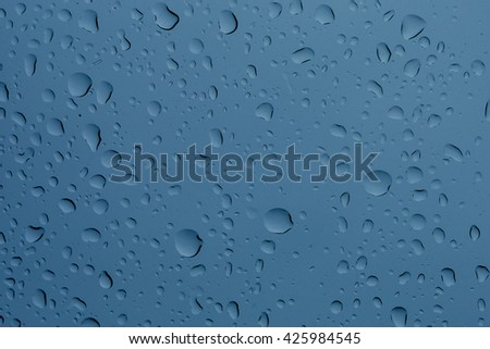 Raindrops on the window glass. Drops of rain on a window glass. Big raindrop on the window in blue. In front of out of focus background. - stock photo