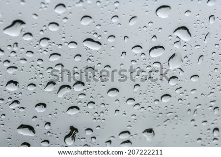 Raindrops on the windshield of a car closeup