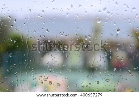 raindrops on window with garden and sea in background - stock photo