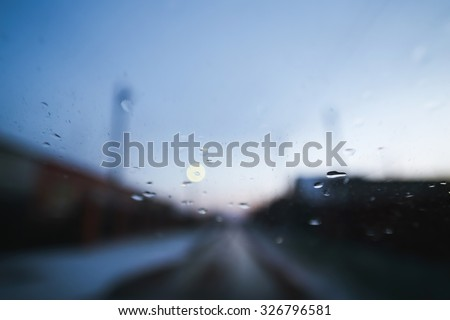 Raindrops on windshield of moving car on countryside road - stock photo