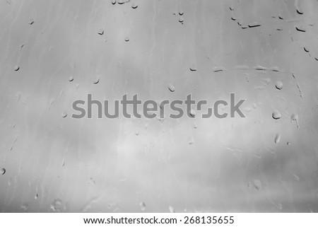 Raindrops, Water drops on a dusty window in monochrome - stock photo