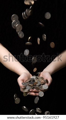 Raining coins in hands towards black background - stock photo