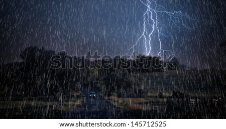 Rainstorm over asphalt road - stock photo