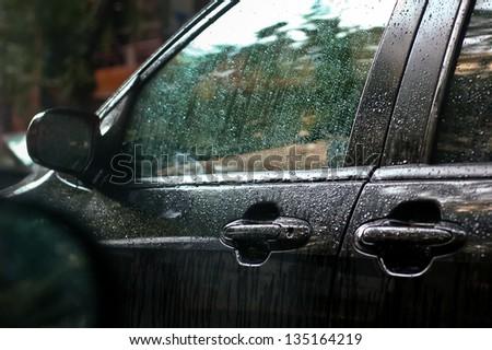 Rainwater trickling down the window pane of a black car waiting in the traffic at intense rain - stock photo