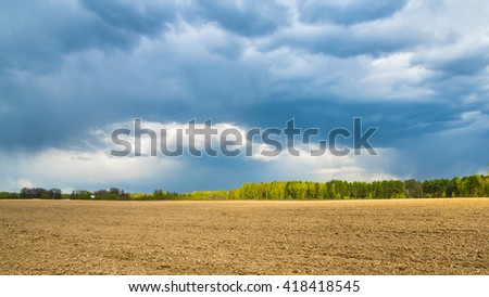 Rainy clouds over spring field - stock photo