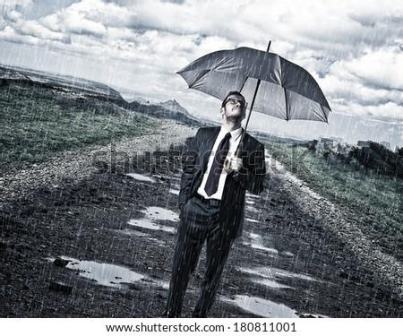 rainy day and man with umbrella on road - stock photo