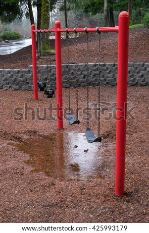 Rainy day at the park playground, red and black swing set  - stock photo