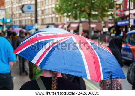 rainy day in London with a woman wearing an umbrella with the flag of Great Britain - stock photo