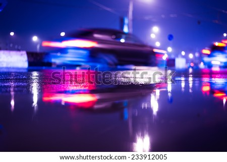Rainy day in the city at night, moving cars