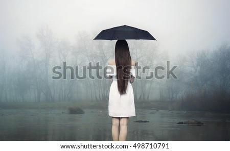 Rainy day. Woman with umbrella standing on the stone et the river. Girl in white dress.