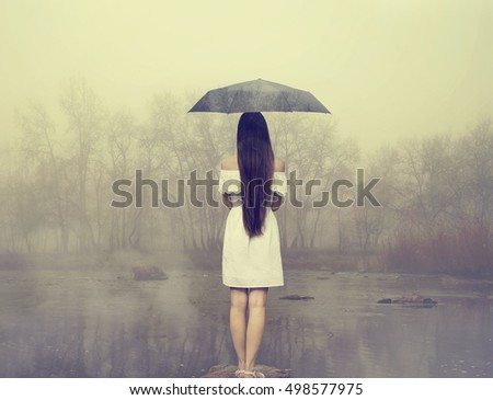 Rainy day. Woman with umbrella standing on the stone et the river. Girl in white dress. The image with the effect of double exposure