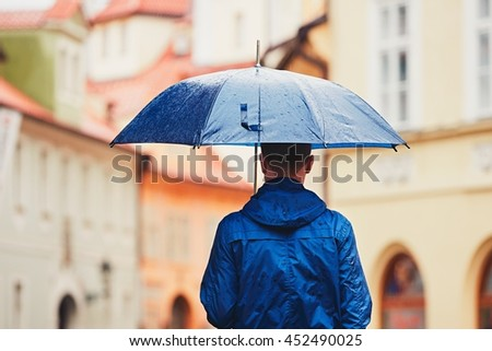 Rainy day. Young man is holding blue umbrella and walking in rain. Street of Prague, Czech Republic. - stock photo