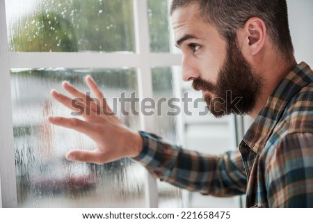 Rainy mood. Thoughtful young bearded man touching the window and looking through it - stock photo