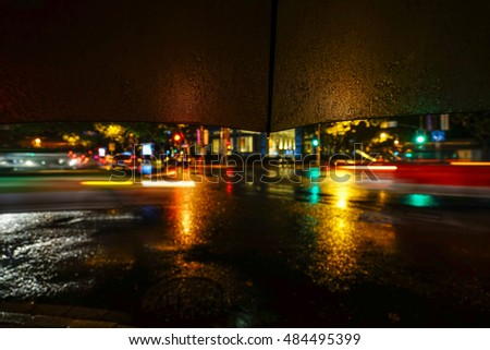 Rainy night. Close up view of the drop on the umbrella during rain.City life in night in rainy season abstract background.