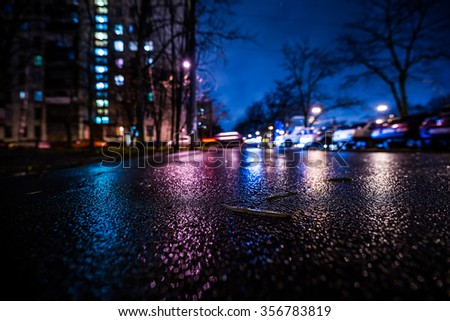 Rainy night in the big city, alley in the city. View from a wide angle at the level of asphalt, in blue tones - stock photo