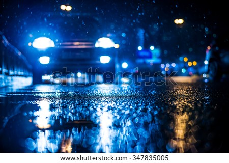 Rainy night in the big city, approaching headlights of car traveling along the avenue. View from the level of the curb on the road, in blue tones - stock photo