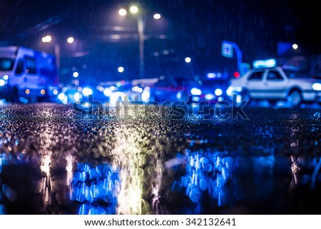 Rainy night in the big city, dense traffic at a busy intersection, headlights of passing cars. View from the level of asphalt, in blue tones - stock photo