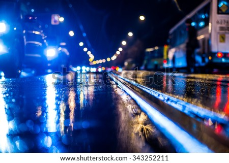 Rainy night in the big city, stream of cars traveling along the avenue and pedestrians on the road. View from the tram rail level, in blue tones - stock photo