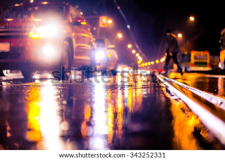 Rainy night in the big city, stream of cars traveling along the avenue and pedestrians on the road. View from the tram rail level, image in the soft orange-purple toning