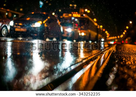 Rainy night in the big city, stream of cars traveling along the avenue. View from the tram rail level - stock photo