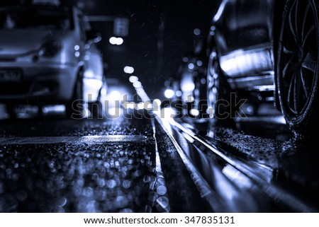 Rainy night in the big city, stream of cars traveling along the avenue. View from the tram rail level, image in the blue toning - stock photo