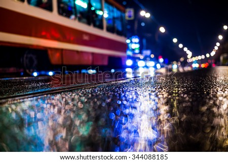 Rainy night in the big city, tram rides along the avenue. View from the tram rail level, in blue tones - stock photo