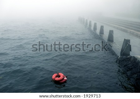 rainy stormy weather on the embankment and life buoy in water - stock photo