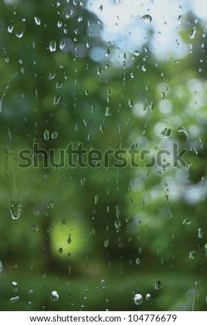 Rainy summer day, raindrops on window glass close up, macro closeup - stock photo