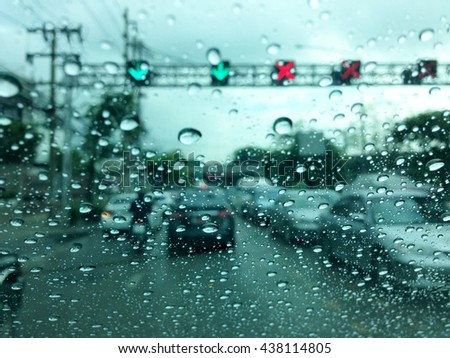 Rainy traffic jam.Street Lights Out Of Focus.Raindrops windshield.Raindrops on the windshield.blurred image of traffic view through a car windscreen covered in rain.   - stock photo