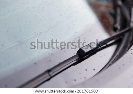 rainy weather and vehicles concept - close up of windshield wiper and wet car glass - stock photo