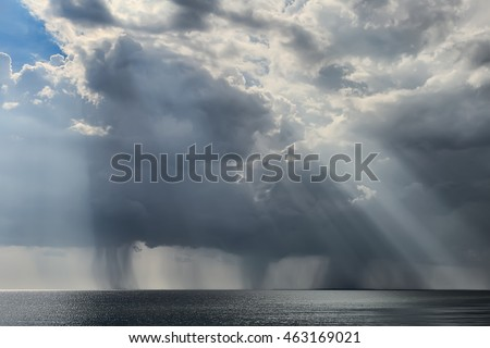 Rainy weather over the sea. Thunderclouds over the seascape and rays of sun.