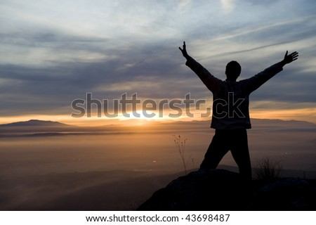 Raised arms man against beautiful sunset. - stock photo