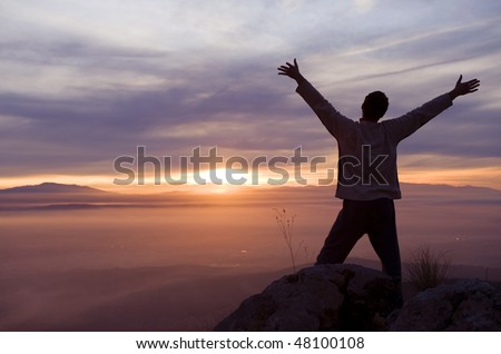 Raised arms man against beautiful sunset - stock photo