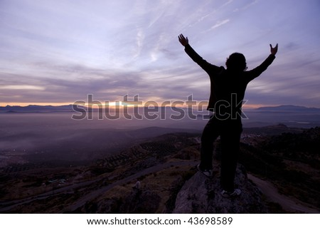 Raised arms man in the summit of mountain against beautiful sunset - stock photo