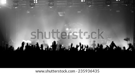 raised hands at a concert facing the stage - stock photo