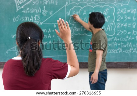 Raised hands in classroom at School - stock photo