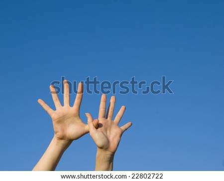 Raised hands on blue sky background - stock photo