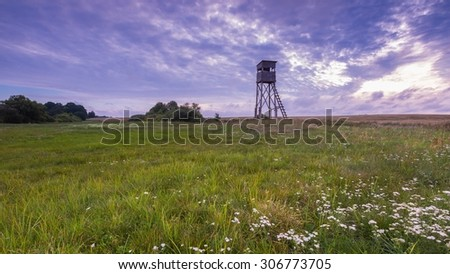 Raised hide on morning meadow under cloudy sky. Beautiful rural landscape