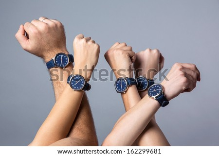 Raised up human hands in a 	 spontaneous movement  of unity wearing identical watches  - stock photo