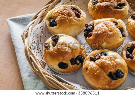 raisin bread in basket and pastel silk on wood table - stock photo